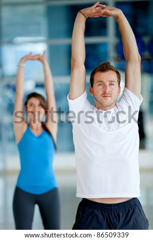 people at the gym stretching their arms - stock photo