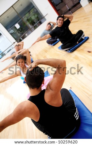 people at the gym taking a class with the trainer - stock photo