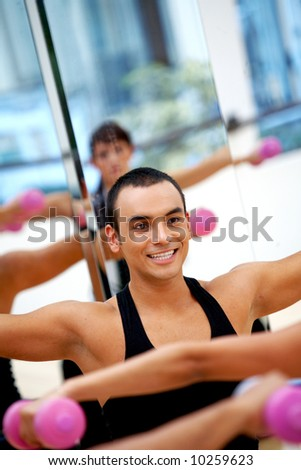 people at the gym taking an aerobics class with the trainer - stock photo