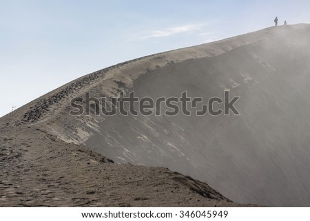 People at the peak of Mount Bromo with some dust smoke came out from the crater - stock photo