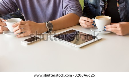 People at White Table of Coffee Shop Holding Mugs and Using Electronic Devices - stock photo