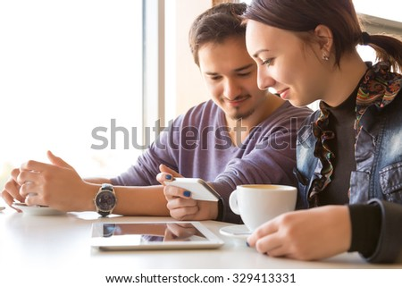People at White Table of Coffee Shop Talking Smiling Using Electronic Devices - stock photo