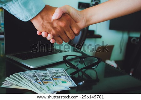 People at work: man and woman hand shaking at a meeting. Closeup shot of a two businesspeople shaking hands, glasses , money, laptop on background. - stock photo