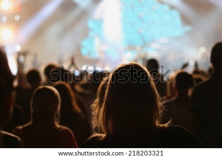 People attending pop concert, silhouettes of crowd dancing in front of stage, shallow DOF - stock photo