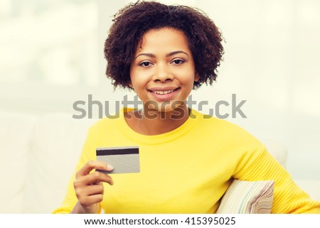 people, bank, shopping and e-money concept - happy african american young woman sitting on sofa with credit or debit card at home - stock photo