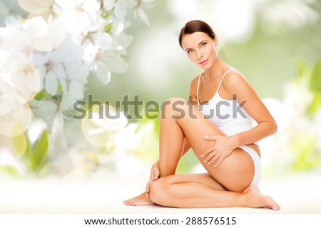 people, beauty and body care concept - beautiful woman in cotton underwear touching her hips over green natural cherry blossom background - stock photo