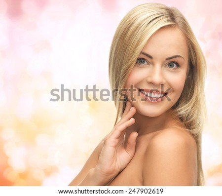 people, beauty, body and skin care concept - beautiful woman face and hands over yellow lights background - stock photo