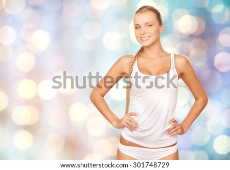 people, beauty, body care and fashion concept - happy beautiful young woman in cotton underwear over blue holidays lights background - stock photo