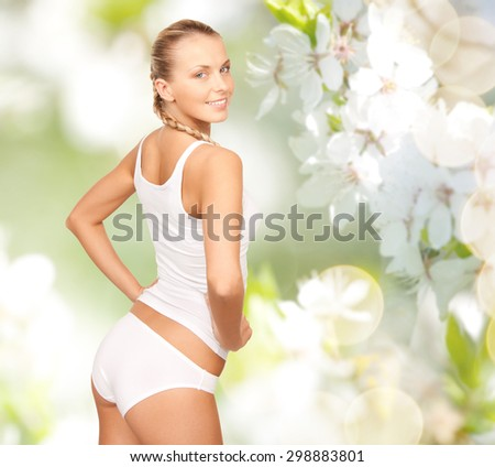people, beauty, body care and health concept - happy beautiful young woman in cotton underwear over green cherry blossom background - stock photo