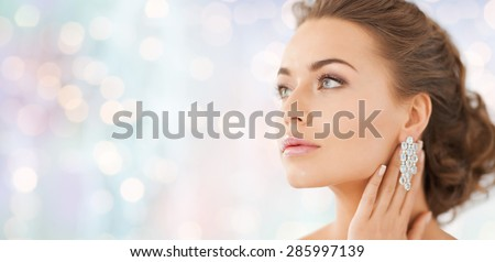 people, beauty, jewelry and accessories concept - beautiful woman with diamond earrings over blue holidays lights background - stock photo