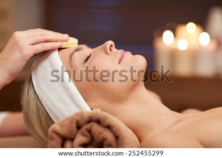people, beauty, spa, cosmetology and relaxation concept - close up of beautiful young woman lying with closed eyes having face cleaning by sponge in spa - stock photo