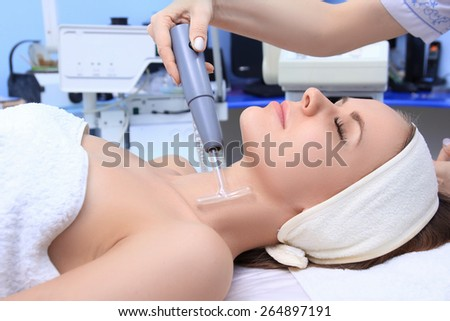 People, beauty, spa, cosmetology and technology concept - close up of beautiful young woman lying with closed eyes having face massage by massager in spa. - stock photo