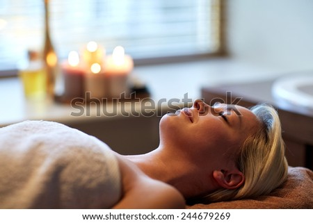 people, beauty, spa, healthy lifestyle and relaxation concept - beautiful young woman lying with closed eyes in spa - stock photo
