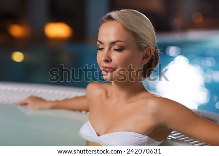 people, beauty, spa, healthy lifestyle and relaxation concept - beautiful young woman wearing bikini swimsuit sitting in jacuzzi at poolside - stock photo