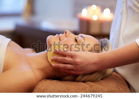 people, beauty, spa, healthy lifestyle and relaxation concept - close up of beautiful young woman lying with closed eyes and having face massage with sponge in spa - stock photo