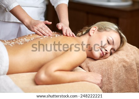 people, beauty, spa, healthy lifestyle and relaxation concept - close up of beautiful young woman lying with closed eyes and having salt massage l in spa - stock photo