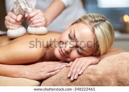 people, beauty, spa, healthy lifestyle and relaxation concept - close up of beautiful young woman lying and having herbal bag massage in spa - stock photo