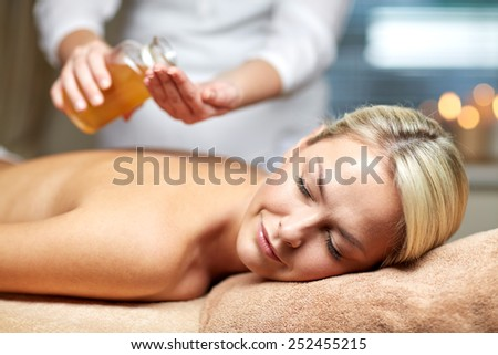 people, beauty, spa, healthy lifestyle and relaxation concept - close up of beautiful young woman lying with closed eyes on massage table and therapist holding oil bottle in spa - stock photo