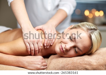 people, beauty, spa, healthy lifestyle and relaxation concept - close up of beautiful young woman lying with closed eyes and having hand massage in spa - stock photo