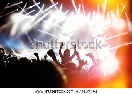 People black silhouettes of concert crowd in front of bright stage lights, guitar on stage