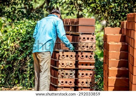 People blue t-shirt with interlocking bricks. Concept for skill or building a team working together, hole in the wall. - stock photo