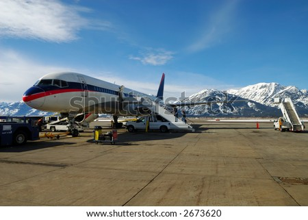 People Boarding a Jet Airplane with snow covered mountains in background - stock photo