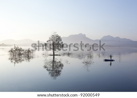 People boating in the reservoir of the dam, Mae Moh in Thailand. - stock photo