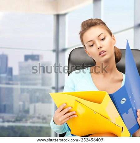 people, business and paperwork concept - young businesswoman with folders sitting on chair over office window background - stock photo