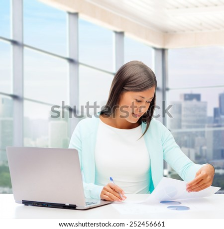 people, business and technology concept - smiling woman with laptop computer sitting at table and reading papers over office window background