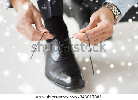 people, business, fashion and footwear concept - close up of man leg and hands tying shoe lace over snow effect - stock photo