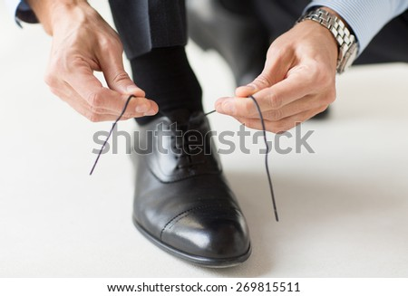 people, business, fashion and footwear concept - close up of man leg and hands tying shoe laces - stock photo