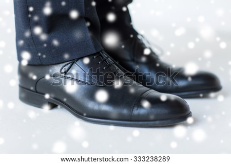 people, business, fashion and footwear concept - close up of man legs in elegant shoes with laces or lace boots over snow effect over snow effect - stock photo