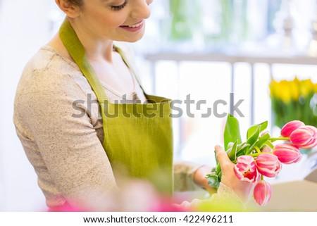 people, business, sale and floristry concept - close up of happy florist woman making tulip bunch at flower shop - stock photo