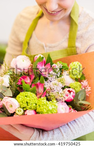 people, business, sale and floristry concept - close up of happy smiling florist woman holding bunch of flowers wrapped into paper at flower shop - stock photo