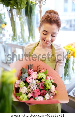 people, business, sale and floristry concept - happy smiling florist woman holding bunch of flowers wrapped into paper at flower shop - stock photo
