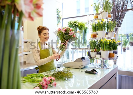 people, business, sale and floristry concept - happy smiling florist woman making bunch and cropping stems by scissors at flower shop - stock photo