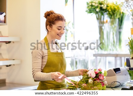 people, business, sale and floristry concept - happy smiling florist woman making bunch at flower shop - stock photo