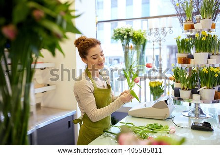 people, business, sale and floristry concept - happy smiling florist woman making tulip bunch at flower shop - stock photo