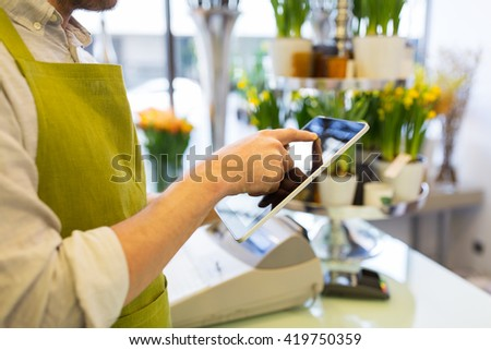 people, business, technology, sale and floristry and concept - close up of florist man with tablet pc computer at flower shop - stock photo