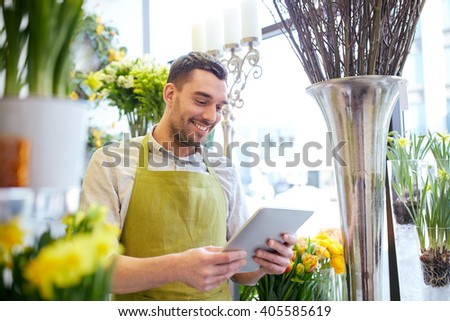 people, business, technology, sale and floristry and concept - happy smiling florist man with tablet pc computer at flower shop - stock photo