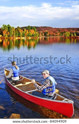 People canoeing on scenic lake in fall, Algonquin park, Canada - stock photo