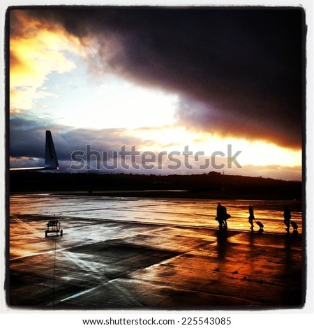 People carrying luggage towards a plane at the airport. - stock photo