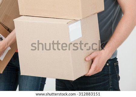 People carrying several cardboard boxes - stock photo