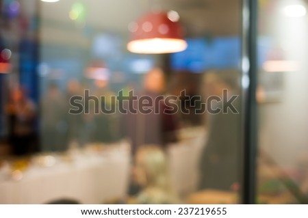 People celebrating dining in cafe through window glass background bokeh - stock photo