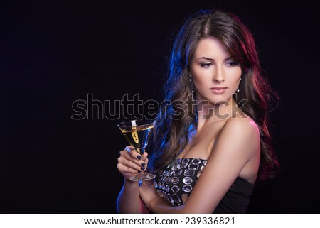 People celebration concept. Closeup of woman with glass of cocktail over dark background looking to the side - stock photo