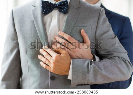 people, celebration, homosexuality, same-sex marriage and love concept - close up of happy male gay couple with wedding rings hugging - stock photo