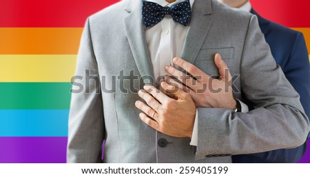 people, celebration, homosexuality, same-sex marriage and love concept - close up of happy male gay couple with wedding rings hugging over rainbow flag background - stock photo