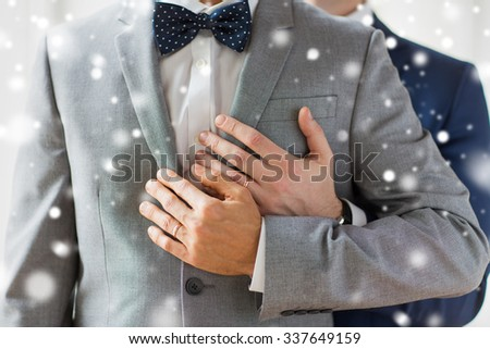 people, celebration, homosexuality, same-sex marriage and love concept - close up of happy male gay couple with wedding rings hugging over snow effect - stock photo