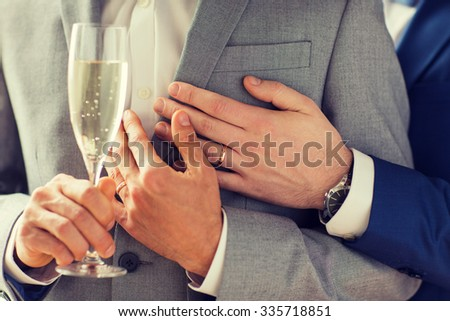 people, celebration, homosexuality, same-sex marriage and love concept - close up of happy married male gay couple in suits drinking sparkling wine from glass on wedding - stock photo
