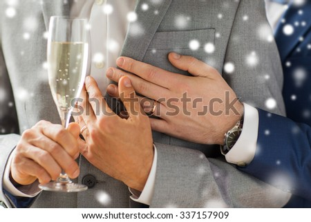 people, celebration, homosexuality, same-sex marriage and love concept - close up of happy married male gay couple in suits drinking sparkling wine from glass on wedding over snow effect - stock photo